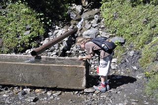 Neunjähriger Junge beim Wandern erfrischt sich an einem Brunnen, Söllereck, Allgäuer Alpen, Bayern, Deutschland, Europa