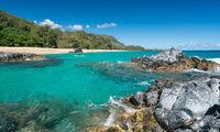 Lumahai Beach Kauai with rocks and surfer
