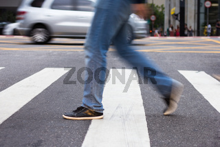 Commuter at zebra walk, busy streets.