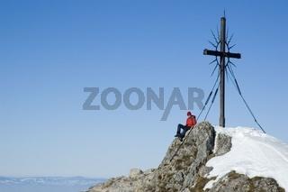 Eine Frau (22) am Gipfelkreuz des 'Steinernen Jäger' in den Voralpen bei Reichraming im Winter