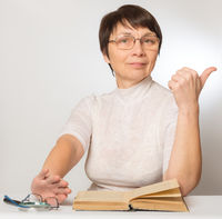 Woman in the new glasses shows a sign that she is doing well and pushes old glasses and a magnifying glass