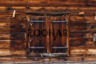 Die geschlossenen Fensterläden einer Hütte in den Alpen.