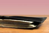 Wad of US dollar bills in black wallet on table