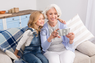 Grandmother and granddaughter making selfie photos