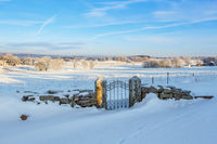 Gate at a stone wall covered with snow