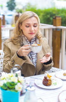 Close up happy adult blond woman with cup of coffee