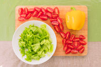 Fresh chopped green lettuce leaves lie on a wooden cutting board next to the yellow bell pepper and chopped red cherry tomatoes on a green table