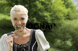 Junge Frau sammelt Wildkraeuter
