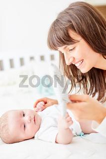 Mutter wechselt fürsorglich die Baby Windeln