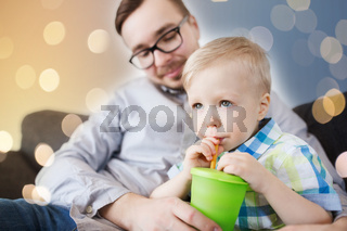 father and son drinking from cup at home