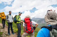 A group of hikers with backpacks and tracking sticks rest and stands in the mountains listening to their guide