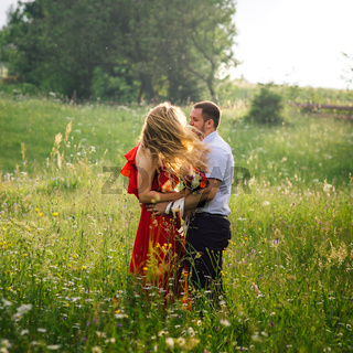 Sunny outdoor portrait of the happy smiling couple hugging on the blooming meadow. The wind is moving the blonde curly hair of the woman.
