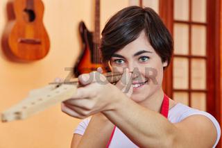 Frau kontrolliert ein Gitarren Griffbrett
