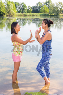 Two women playing together in water