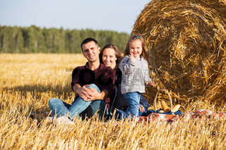 Happy young family with two year old girl next to hay bales in harvested field