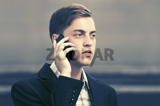 Young handsome business man talking on mobile phone in city street