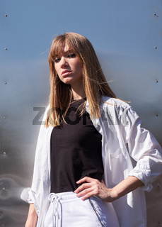 Young blonde woman. Female model posing on metal background