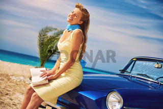Beautiful happy woman with a book near retro cabriolet car on the beach