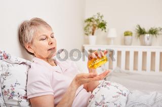 Kranke Seniorin nimmt Tabletten ein