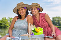 Two women with  picknick basket in nature