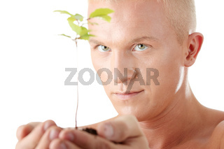 Muscular man holding small plant