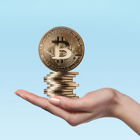 Female hand holds gold coins bitcoin
