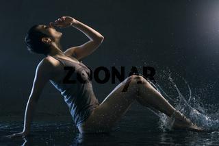 Brunette in wet t-shirt under water in the dark
