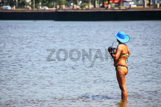 Local woman standing with mate cup by the shore of Rio de la Pla