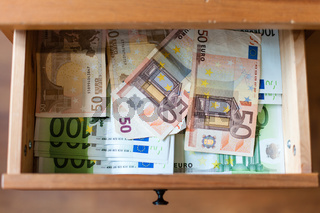 many euro banknotes on bottom of open drawer