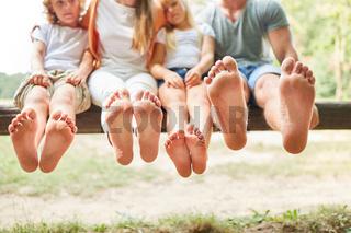 Familie barfuß auf einer Parkbank