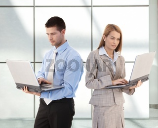 Young businesspeople using laptop in office lobby