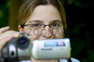 Junge Frau mit Videokamera beim filmen