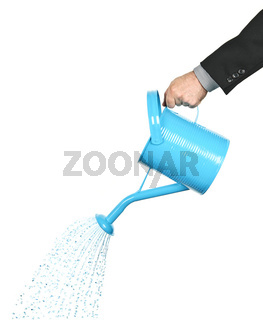 Hand pouring water from watering can