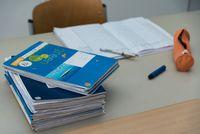 Stapel an Schularbeiten am Lehrertisch beim Korrigieren