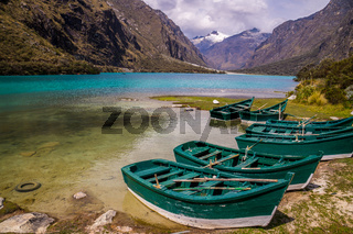 Green boats at glacier lagoon in Peruvian Andes