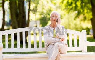 happy senior woman calling on smartphone in summer