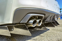 Close up of a dual exhaust pipe on a white car with tail spikes