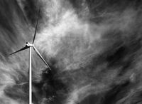 Wind turbine and black and white sky with clouds