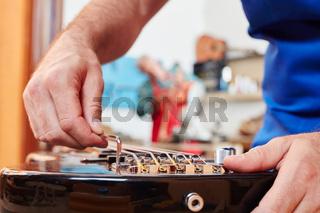 Gitarrenbauer justiert Gitarrensaite am Steg