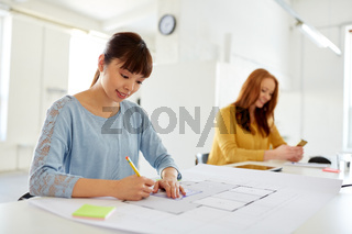 female architect with blueprint working at office
