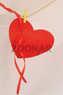 Red paper heart shape hanging on cloth line