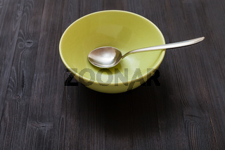 green bowl with steel spoon on dark brown board