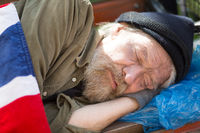 Close up portrait of homeless man sleeping on bench in city park.