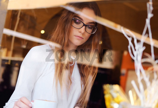 Young brunette drinking a coffee in a restaurant