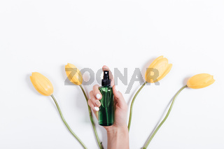 Top view of yellow tulips with green stems and a female hand holding a water bottle