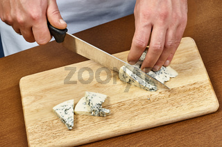cutting cheese on a wooden cooking board