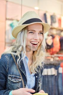 Blonde junge Frau mit Strohhut freut sich