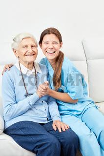 Pflegerin macht Hausbesuch bei glücklicher Seniorin