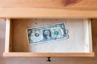 one dollar banknote in open drawer