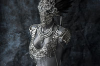 Masquerade, handmade piece, silver jewelry costume with chains and coins. wears a headdress made with feathers and gothic pieces